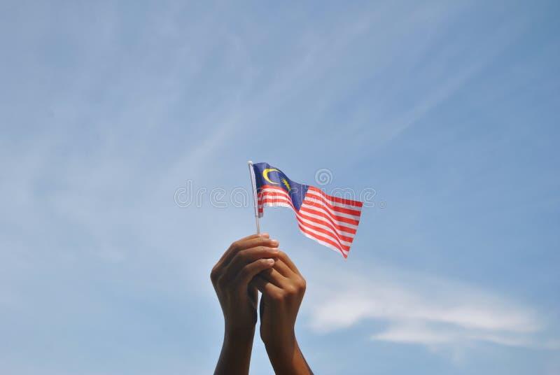 Σημαία της Μαλαισίας εκμετάλλευσης χεριών στοκ φωτογραφία