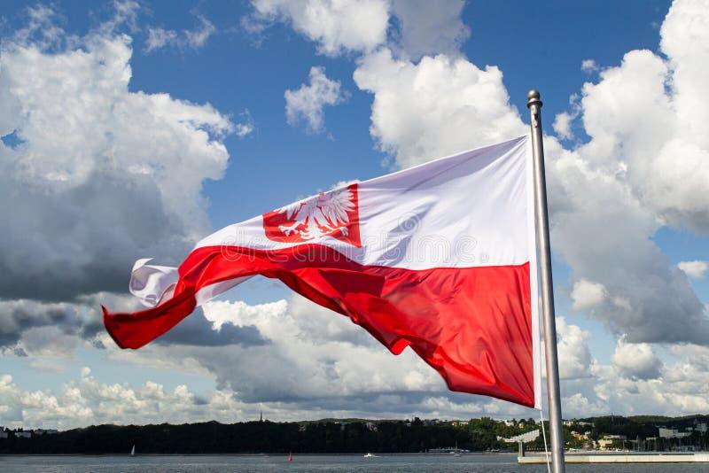 Σημαία της Πολωνίας Εθνική σημαία της Πολωνίας με το έμβλημα στο νεφελώδη μπλε ουρανό Βαλτική ακτή στοκ φωτογραφία με δικαίωμα ελεύθερης χρήσης