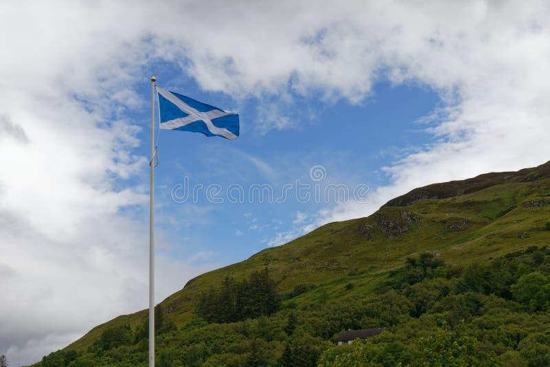 Σημαία της Σκωτίας πάνω από τα βουνά των Highlands στοκ φωτογραφία