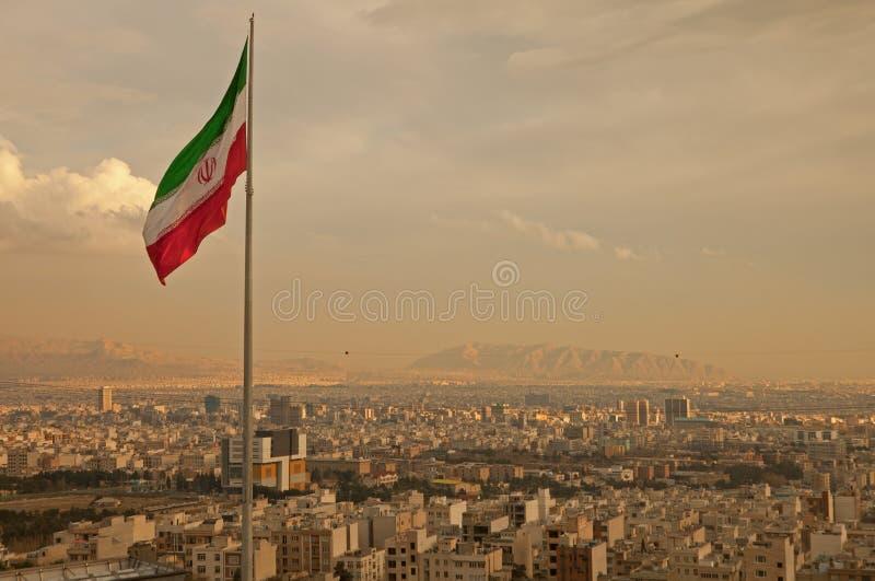 Σημαία του Ιράν στον αέρα επάνω από τον ορίζοντα της Τεχεράνης στοκ φωτογραφία