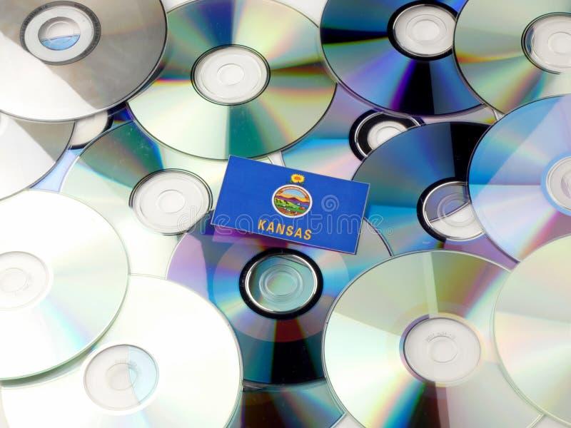 Σημαία του Κάνσας πάνω από το σωρό του CD και DVD στο λευκό στοκ εικόνα