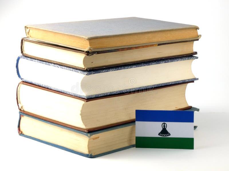 Σημαία του Λεσόθο με το σωρό των βιβλίων στο άσπρο υπόβαθρο στοκ εικόνες