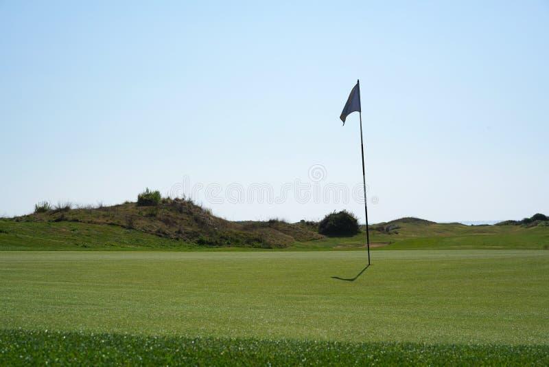 Σημαία τρυπών στο γήπεδο του γκολφ μια ηλιόλουστη ημέρα στοκ φωτογραφίες