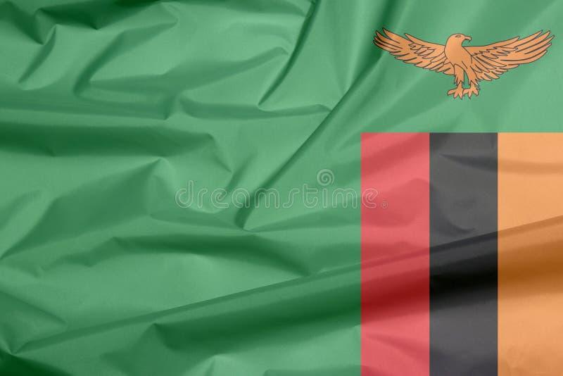 Σημαία υφάσματος της Ζάμπια Πτυχή του της Ζάμπια υποβάθρου σημαιών απεικόνιση αποθεμάτων