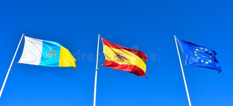 Σημαίες καναρινιών, της Ισπανίας και της ΕΕ σε έναν μπλε ουρανό στοκ φωτογραφίες με δικαίωμα ελεύθερης χρήσης