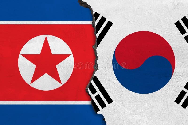 Σημαίες της Βόρεια Κορέας και της Νότιας Κορέας που χρωματίζονται στο ραγισμένο τοίχο ελεύθερη απεικόνιση δικαιώματος