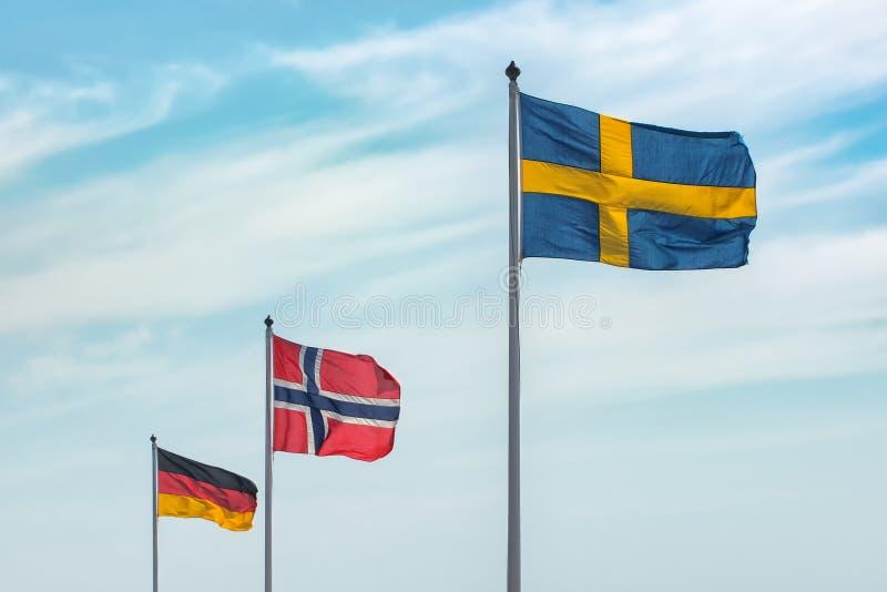 Σημαίες της ΕΕ, Γερμανία, Νορβηγία, Σουηδία στο μπλε ουρανό Έννοιες της πολιτικής, του τουρισμού, της οικονομίας, της συνεργασίας στοκ εικόνες