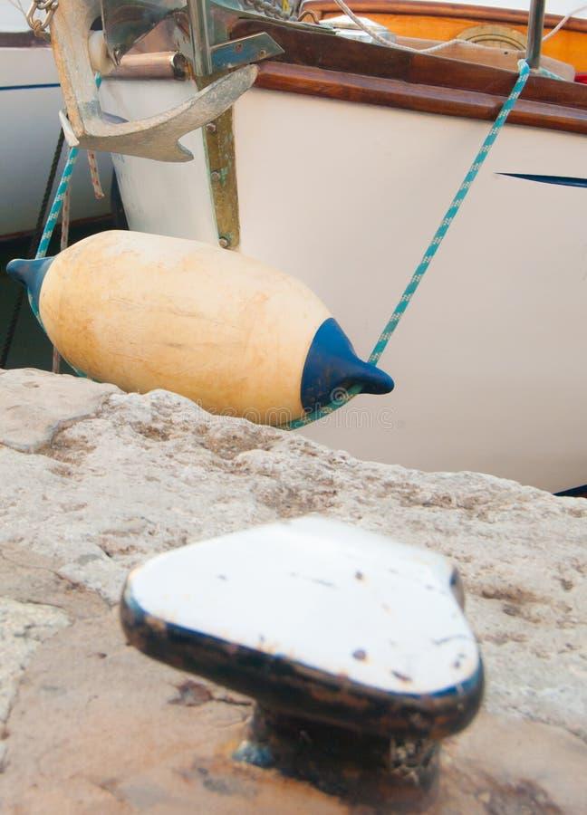 Σημαντήρας άσπρος και μπλε σε μια πλέοντας φλούδα και μια δένοντας στήλη στοκ φωτογραφία με δικαίωμα ελεύθερης χρήσης