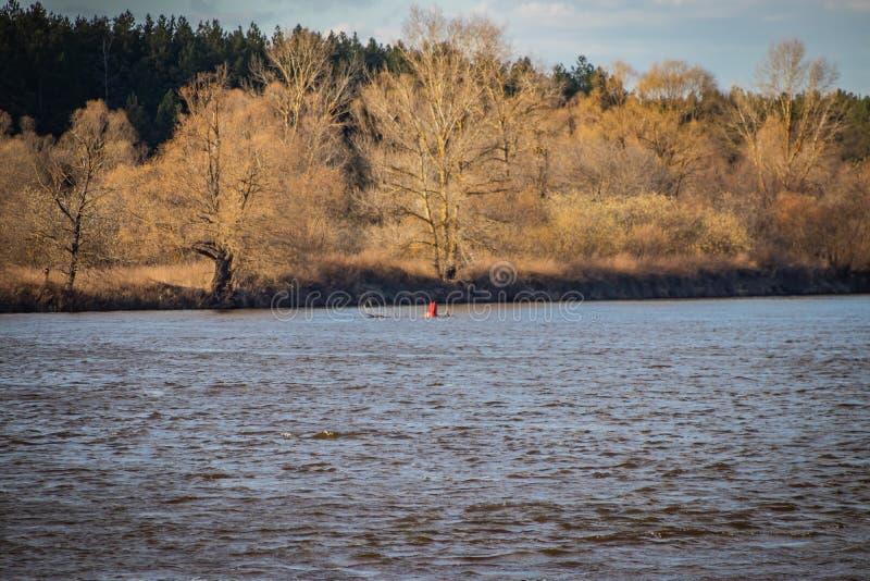 Σημαντήρας σε έναν πλεύσιμο ποταμό, που προειδοποιεί για τον κίνδυνο στα σκάφη στοκ εικόνα