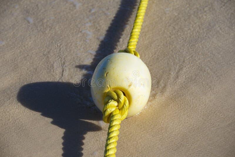 Σημαντήρας σε ένα κίτρινο σχοινί που βρίσκεται στην υγρή άμμο στοκ εικόνες