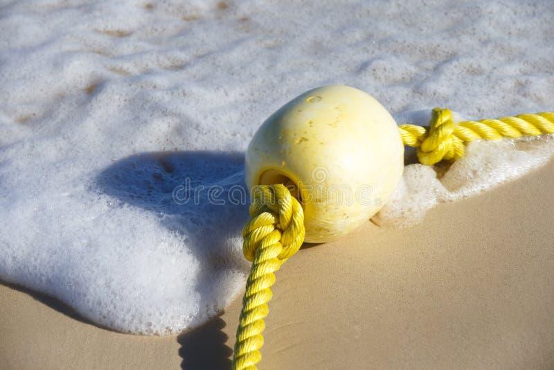 Σημαντήρας σε ένα κίτρινο σχοινί που βρίσκεται στην υγρή άμμο στοκ εικόνες με δικαίωμα ελεύθερης χρήσης