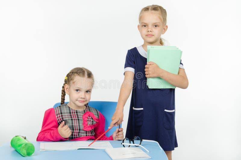 Σημεία δασκάλων κοριτσιών στο σημειωματάριο σπουδαστών στοκ εικόνες