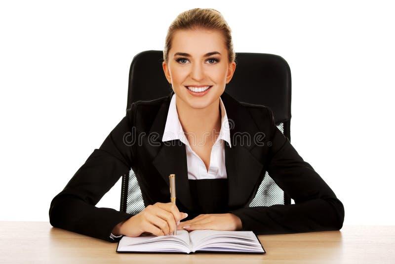 Σημείωση γραψίματος επιχειρηματιών χαμόγελου από ένα γραφείο στοκ φωτογραφία με δικαίωμα ελεύθερης χρήσης
