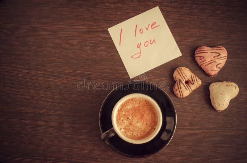 Σημείωση σ' αγαπώ με το φλιτζάνι του καφέ και τα μπισκότα στοκ εικόνα