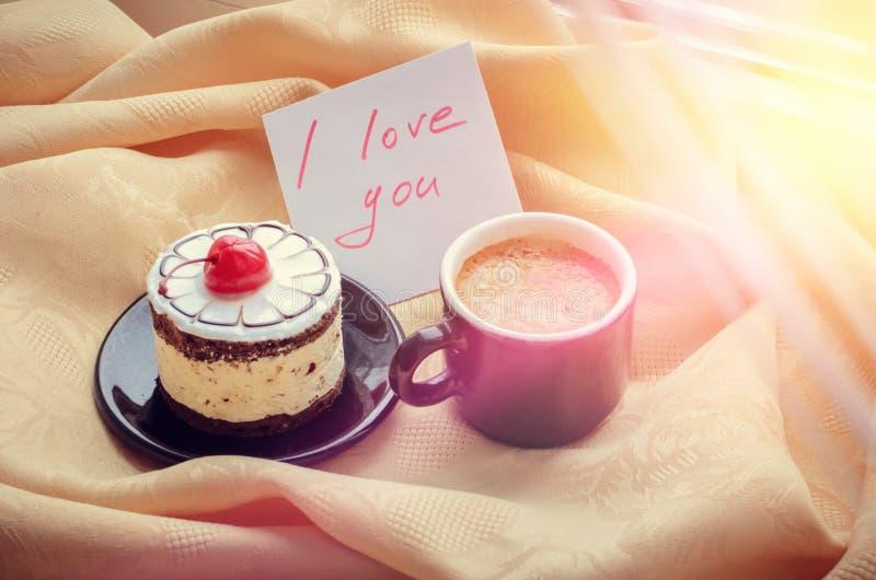 Σημείωση σ' αγαπώ με το φλιτζάνι του καφέ και το κέικ στοκ εικόνες