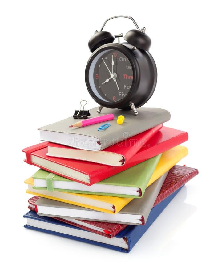 Σημειωματάρια και ξυπνητήρι στο άσπρο υπόβαθρο στοκ εικόνα