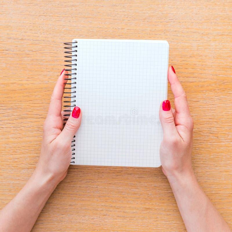 Σημειωματάριο εκμετάλλευσης χεριών γυναικών στοκ εικόνες