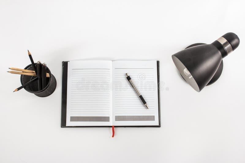 Σημειωματάριο, επιτραπέζιος λαμπτήρας, και στάσιμος στο χώρο εργασίας στοκ φωτογραφίες