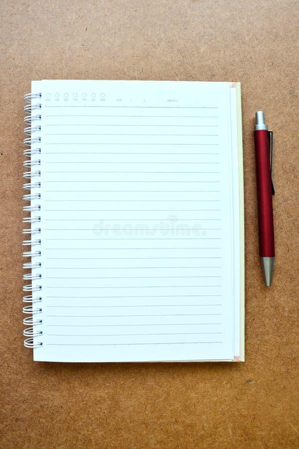 Σημειωματάριο και κόκκινη μάνδρα στο ξύλινο υπόβαθρο στοκ φωτογραφία με δικαίωμα ελεύθερης χρήσης