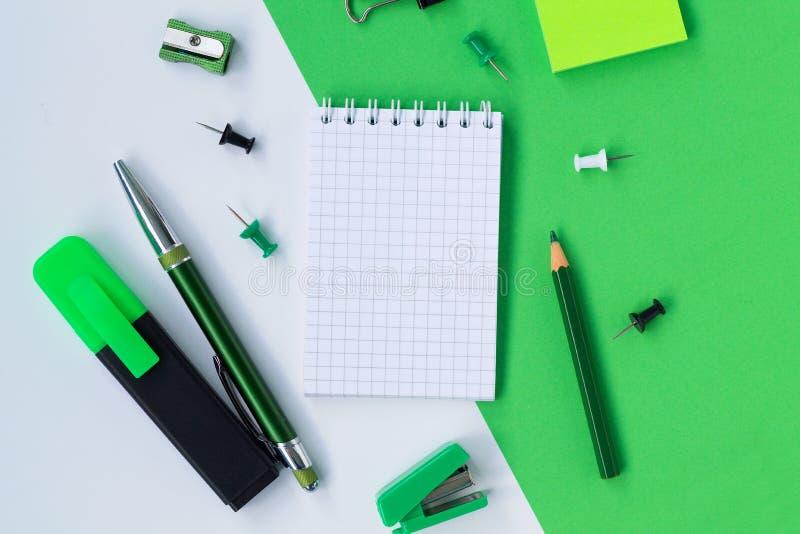 Σημειωματάριο και μολύβια με άλλες σχολικές προμήθειες που απομονώνονται στο άσπρο και πράσινο υπόβαθρο o στοκ εικόνα