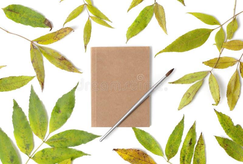 Σημειωματάριο και πράσινα φύλλα στοκ εικόνα με δικαίωμα ελεύθερης χρήσης