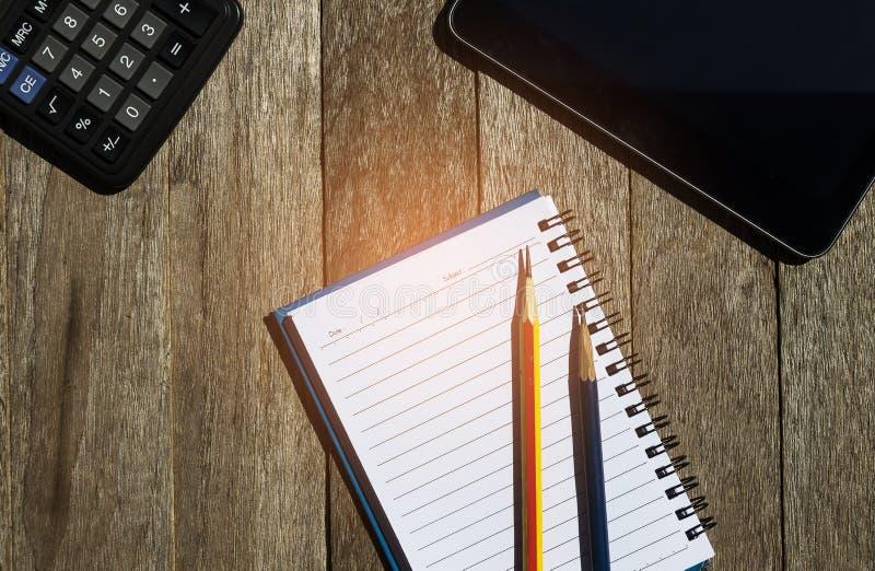 σημειωματάριο κενών σελίδων στο ξύλινο υπόβαθρο με το έξυπνο τηλέφωνο και calc στοκ εικόνα