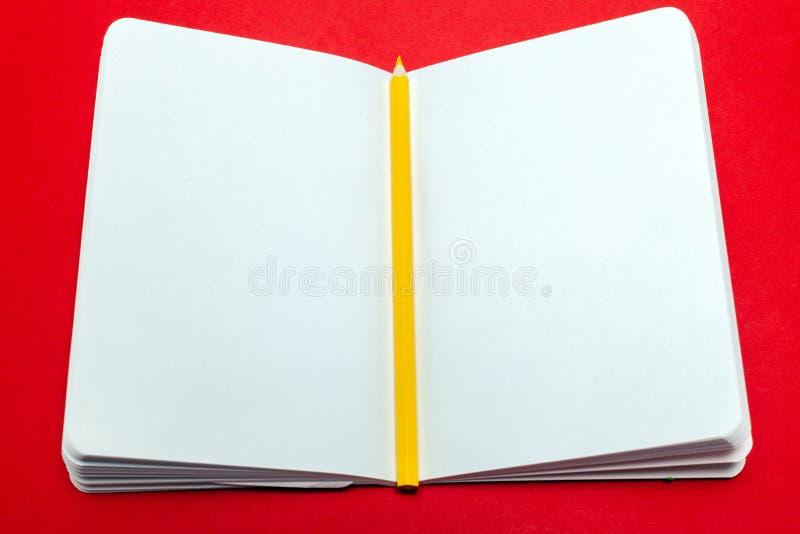 Σημειωματάριο κινηματογραφήσεων σε πρώτο πλάνο και κίτρινο μολύβι με την κενή Λευκή Βίβλο φύλλων για το κόκκινο υπόβαθρο Έννοια ε στοκ εικόνα με δικαίωμα ελεύθερης χρήσης