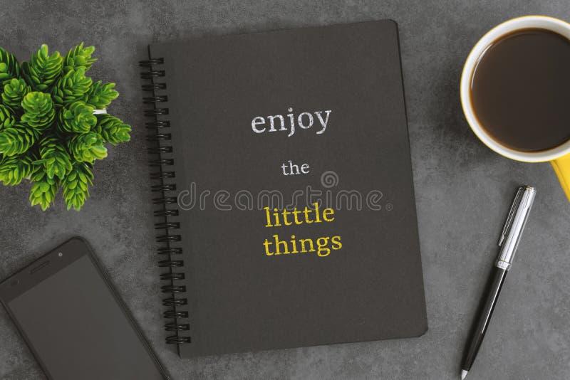 Σημειωματάριο, κινητό φλυτζάνι τηλεφώνων, μανδρών και καφέ στο σκούρο γκρι υπόβαθρο Σύντομο απόσπασμα για τη ζωή στοκ φωτογραφίες