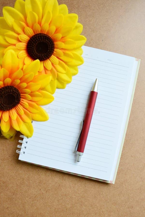 Σημειωματάριο, κόκκινοι μάνδρα και ηλίανθος στο ξύλινο υπόβαθρο στοκ εικόνα με δικαίωμα ελεύθερης χρήσης