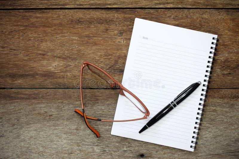 Σημειωματάριο, μάνδρα και γυαλιά στο εκλεκτής ποιότητας ξύλο στοκ φωτογραφία