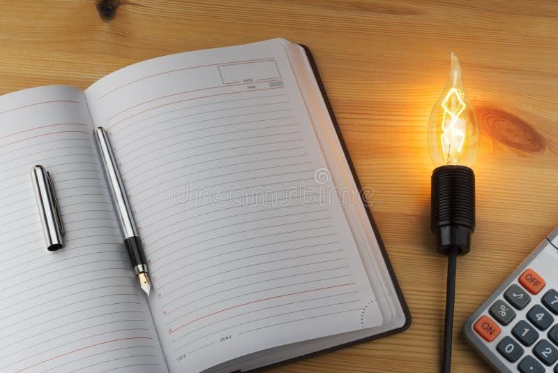 Σημειωματάριο, μάνδρα, υπολογιστής, και ένας καίγοντας λαμπτήρας σε μια ξύλινη επιφάνεια στοκ εικόνα