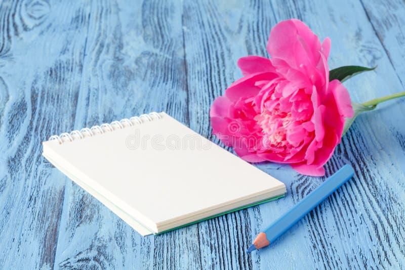 Σημειωματάριο με ένα μολύβι και peonies λουλούδια στο ξύλινο backgro στοκ φωτογραφία