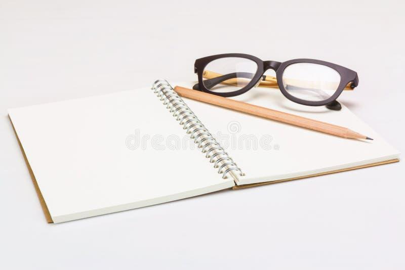 Σημειωματάριο με τα γυαλιά μολυβιών και ματιών στοκ εικόνες