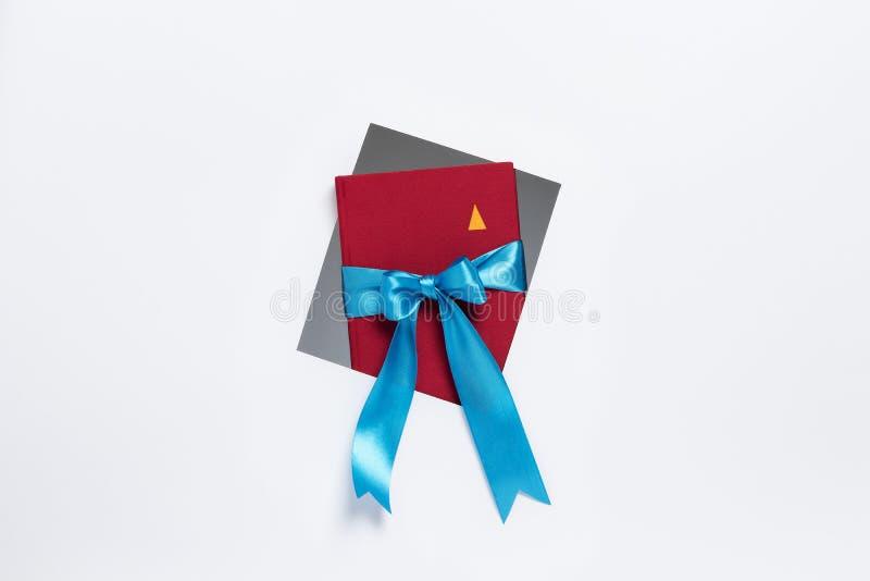 Σημειωματάριο με την κορδέλλα δώρων που βγαίνει από το πλαίσιο στο άσπ στοκ φωτογραφία