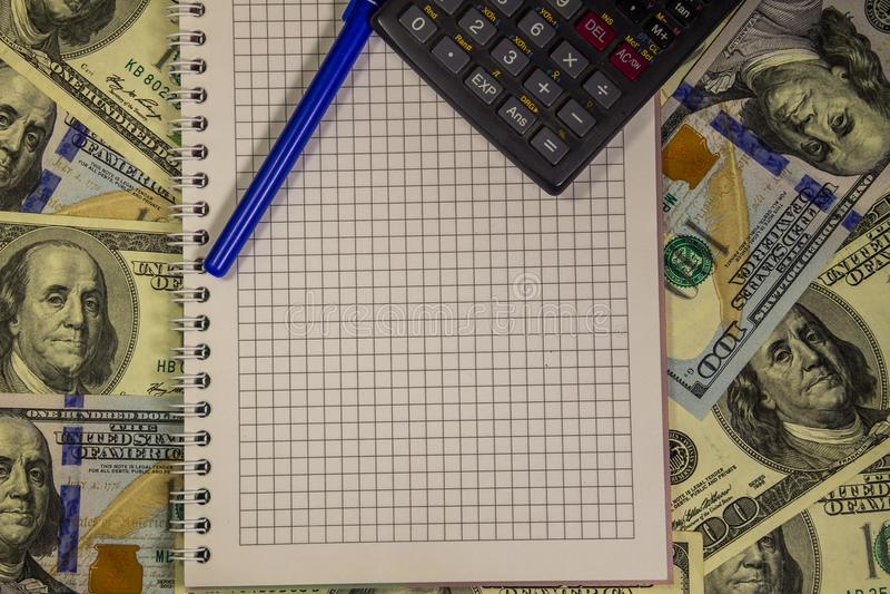 Σημειωματάριο με τη μάνδρα και υπολογιστής στους αμερικανικούς λογαριασμούς εκατό δολαρίων στοκ εικόνες