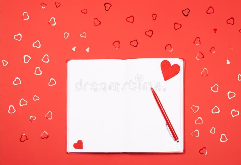 Σημειωματάριο με τη μάνδρα στο κόκκινο υπόβαθρο με το καρδιά-διαμορφωμένο κομφετί στοκ φωτογραφία