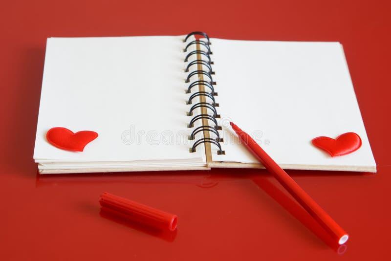 Σημειωματάριο με τις καρδιές και μια κόκκινη μάνδρα πίλημα-ακρών σε ένα κόκκινο υπόβαθρο Προετοιμασία για τα συγχαρητήρια την ημέ στοκ εικόνες με δικαίωμα ελεύθερης χρήσης