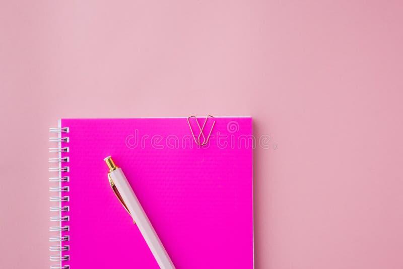 Σημειωματάριο με τους πλαστικούς ρόδινους συνδετήρες κάλυψης, μανδρών και εγγράφου χρώματος Θηλυκό σύνολο Ρόδινη ανασκόπηση Εκλεκ στοκ φωτογραφία