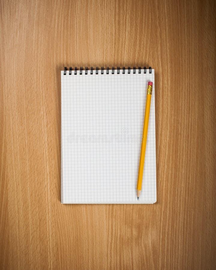 Σημειωματάριο με το μολύβι στο ξύλινο υπόβαθρο στοκ εικόνα με δικαίωμα ελεύθερης χρήσης