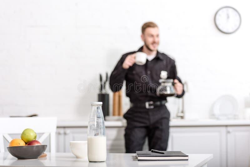 σημειωματάριο, μπουκάλι γάλακτος, κύπελλο των φρούτων στον πίνακα κουζινών και αστυνομικός στοκ εικόνες