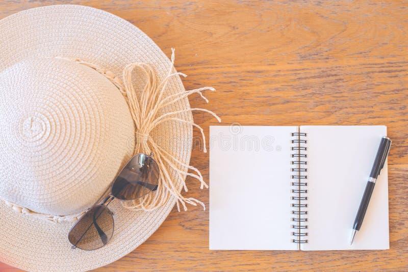 Σημειωματάριο στην κενή οθόνη με τη μάνδρα, καπέλο αχύρου, γυαλιά ηλίου σε ξύλινο στοκ εικόνες