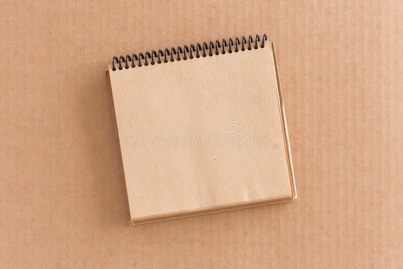 Σημειωματάριο στο υπόβαθρο χαρτονιού στοκ φωτογραφία με δικαίωμα ελεύθερης χρήσης