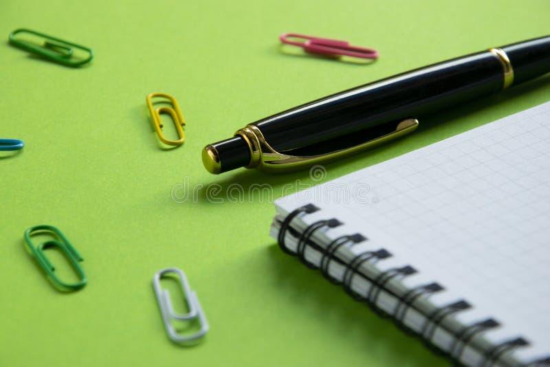 Σημειωματάριο, συνδετήρες εγγράφου και μάνδρα προμήθειες στις πράσινες επιφάνειας γραφείων, πίσω στο σχολείο στοκ φωτογραφία