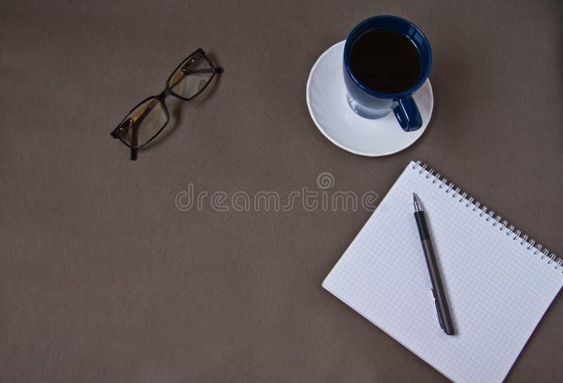 Σημειωματάριο, φλυτζάνι καφέ, γυαλιά, προμήθειες γραφείων στοκ φωτογραφία με δικαίωμα ελεύθερης χρήσης
