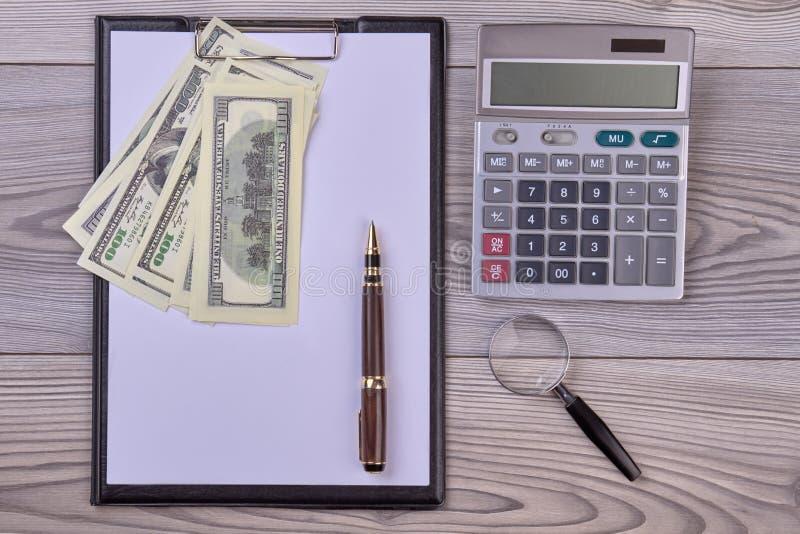 Σημειωματάριο, χρήματα, υπολογιστής και ξύλινος πίνακας με το διάστημα αντιγράφων στοκ εικόνες