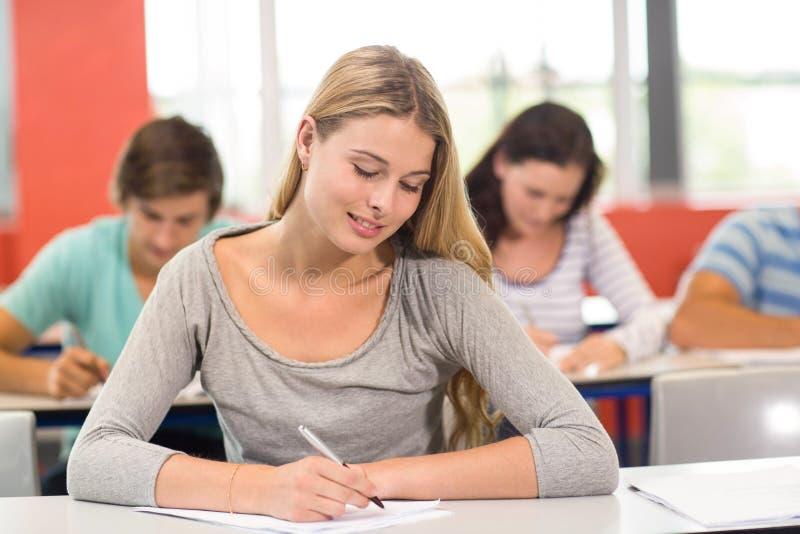 Σημειώσεις γραψίματος γυναικών σπουδαστών στην τάξη στοκ εικόνες