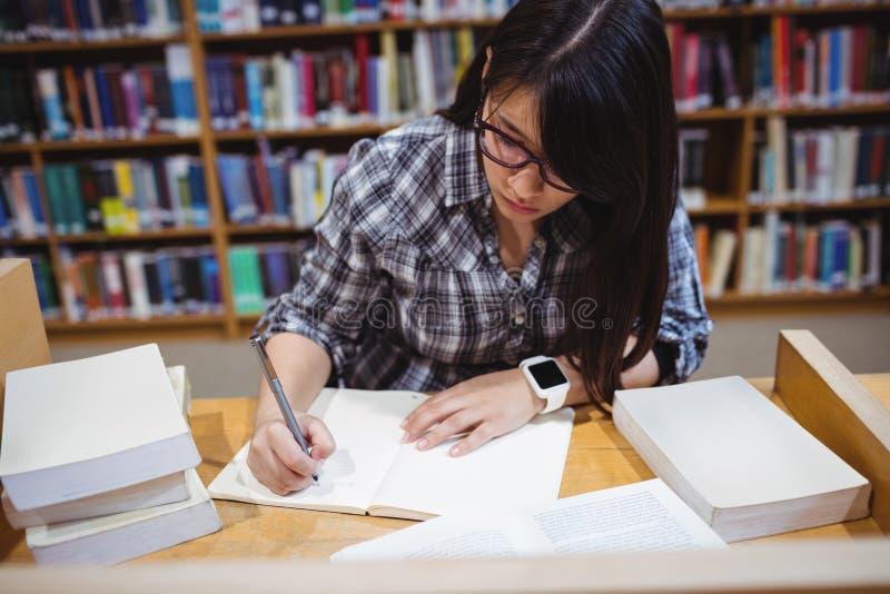 Σημειώσεις γραψίματος γυναικών σπουδαστών στη βιβλιοθήκη στοκ φωτογραφία
