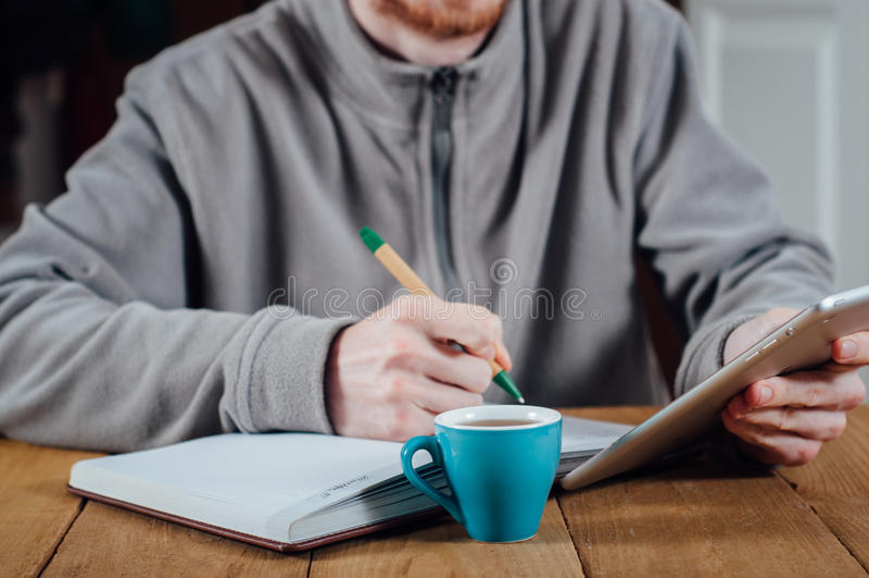 Σημειώσεις γραψίματος νεαρών άνδρων που χρησιμοποιούν το PC ταμπλετών στοκ εικόνα με δικαίωμα ελεύθερης χρήσης