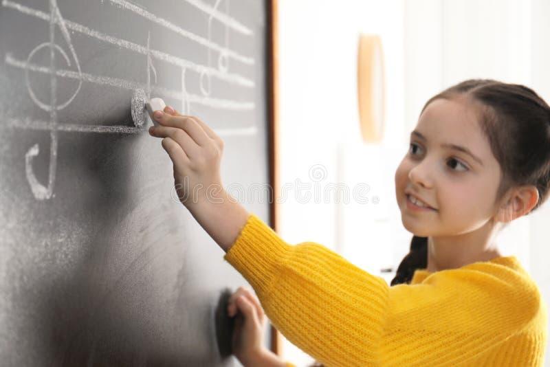 Σημειώσεις μουσικής γραψίματος μικρών κοριτσιών για τον πίνακα στην τάξη στοκ εικόνες