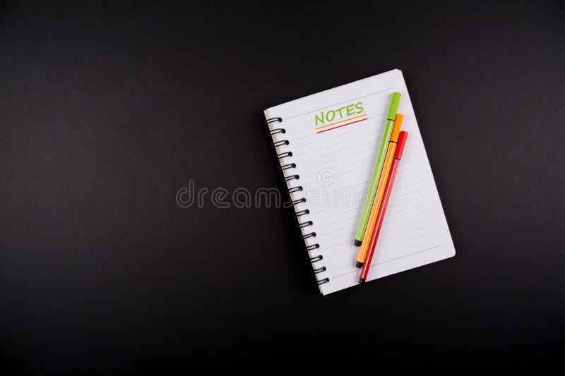 Σημειώσεις, σημειωματάριο και τρεις μάνδρες κόκκινες, πράσινες και πορτοκαλιές, στο μαύρο υπόβαθρο στοκ εικόνες